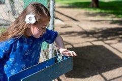 Menina no vestido azul usando a fonte bebendo foto de stock