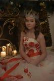 Menina no vestido branco com flores vermelhas, chaminé com velas iluminadas imagem de stock royalty free