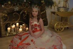 Menina no vestido branco com flores vermelhas, chaminé com velas iluminadas foto de stock