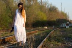 A menina no vestido branco com os pés descalços com sapatas vai à disposição ao longo da estrada de ferro Imagem de Stock Royalty Free