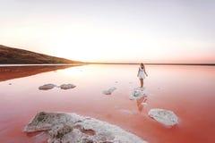 A menina no vestido branco no lago a cor do coral de vida, imagens de stock royalty free