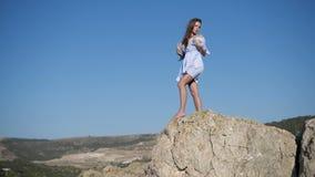 A menina no vestido branco levanta contra um céu azul claro filme