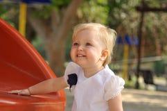 Menina no vestido branco no campo de jogos Fotos de Stock Royalty Free