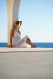 Menina no vestido branco no por do sol pelo mar Fotografia de Stock Royalty Free