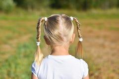 A menina no vestido branco olha para a frente no campo, vista traseira, close-up fotografia de stock royalty free