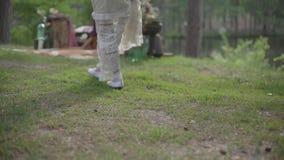 Menina no vestido branco que anda na grama verde na floresta video estoque