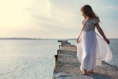 Menina no vestido branco que está na ponte Foto de Stock Royalty Free