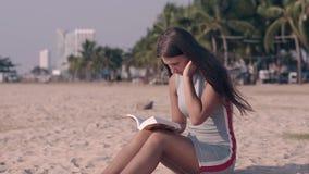 Menina no vestido cinzento do verão com as listras vermelhas e brancas na areia vídeos de arquivo