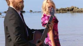 a menina no vestido com curva flerta a dança pelo guitarrista na praia video estoque