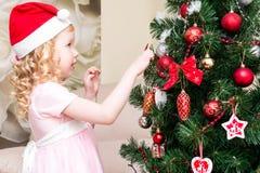 Menina no vestido cor-de-rosa que decora a árvore de Natal Fotografia de Stock