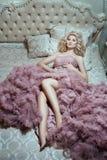 Menina no vestido cor-de-rosa que encontra-se em uma cama luxúria Fotografia de Stock