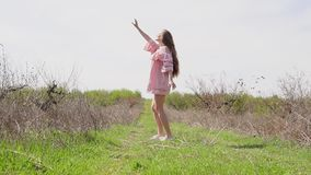 Menina no vestido cor-de-rosa que levanta no jardim vídeos de arquivo