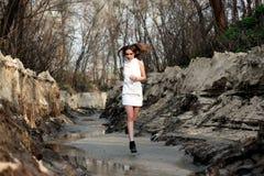 A menina no vestido curto branco corre na areia Imagem de Stock Royalty Free