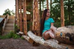 Menina no vestido curto de turquesa que senta-se em um log da árvore foto de stock