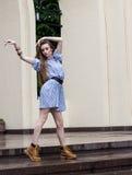 Menina no vestido curto e botas que dançam na cidade Imagens de Stock Royalty Free