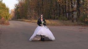 A menina no vestido de casamento com uma máscara do crânio em sua cara está correndo em uma estrada vazia filme