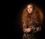 Menina no vestido do leopardo e em sapatas pretas no fundo marrom Fotografia de Stock Royalty Free