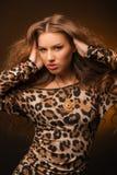 Menina no vestido do leopardo e em sapatas pretas no fundo marrom Fotos de Stock