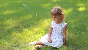 Menina no vestido do verão e com a aro do cabelo que senta-se na grama verde no parque vídeos de arquivo