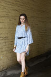 A menina no vestido e nas botas anda na cidade Fotos de Stock Royalty Free