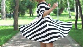 A menina no vestido está andando felizmente com o parque e o giro do verão Retrato de uma menina em um vestido do verão e filme