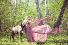 Menina no vestido feericamente com um trem de fluxo no vestido e na rena Imagem de Stock