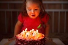 Menina no vestido festivo para fora as velas no bolo o aniversário do ` s da criança foto de stock