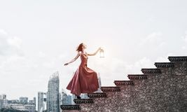 Menina no vestido longo que vai acima a escadaria Meios mistos fotos de stock