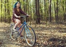 A menina no vestido monta uma bicicleta atrav?s da floresta fotografia de stock