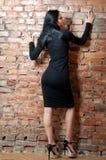 Menina no vestido preto curto Parede de tijolo imagem de stock royalty free