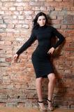 Menina no vestido preto curto Parede de tijolo fotos de stock royalty free