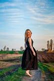 A menina no vestido preto está dançando no campo com os pés descalços Imagens de Stock Royalty Free