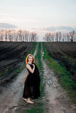 A menina no vestido preto está estando no campo com os pés descalços Fotos de Stock