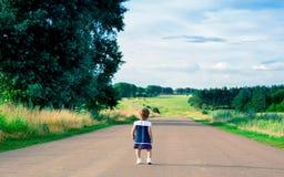 Menina no vestido que anda em uma estrada secundária Fotografia de Stock Royalty Free