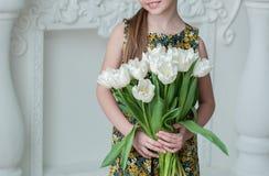 Menina no vestido que guarda muitas tulipas brancas em um fundo branco fotos de stock royalty free