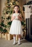 A menina no vestido que guarda presentes aproxima a árvore de Natal fotos de stock royalty free