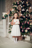 A menina no vestido que guarda presentes aproxima a árvore de Natal foto de stock royalty free
