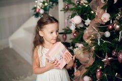 A menina no vestido que guarda presentes aproxima a árvore de Natal fotos de stock