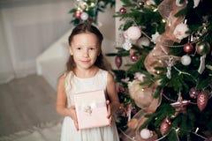 A menina no vestido que guarda presentes aproxima a árvore de Natal imagens de stock royalty free