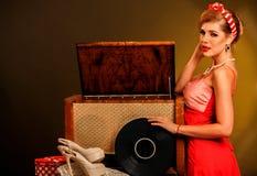 A menina no vestido retro vermelho do estilo mantém o registro de vinil Imagem de Stock Royalty Free