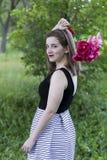 Menina no vestido sem mangas que guarda o ramalhete sobre seu ombro fotografia de stock royalty free