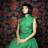 Menina no vestido verde, cercado por rosas Fotografia de Stock