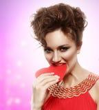 A menina no vestido vermelho come o coração. O dia de Valentim fotos de stock royalty free