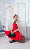 A menina no vestido vermelho está sentando-se em uma mala de viagem na frente de um fol Foto de Stock Royalty Free