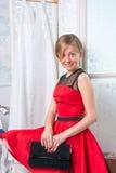 A menina no vestido vermelho está sentando-se em uma mala de viagem na frente de um fol Imagem de Stock Royalty Free