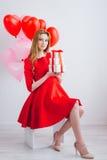 A menina no vestido vermelho guarda caixas com presentes Imagens de Stock Royalty Free