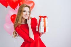 A menina no vestido vermelho guarda caixas com presentes Foto de Stock