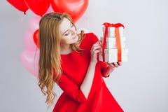 A menina no vestido vermelho guarda caixas com presentes Fotos de Stock Royalty Free