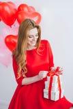 A menina no vestido vermelho guarda caixas com presentes Foto de Stock Royalty Free