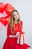 A menina no vestido vermelho guarda caixas com presentes Imagens de Stock